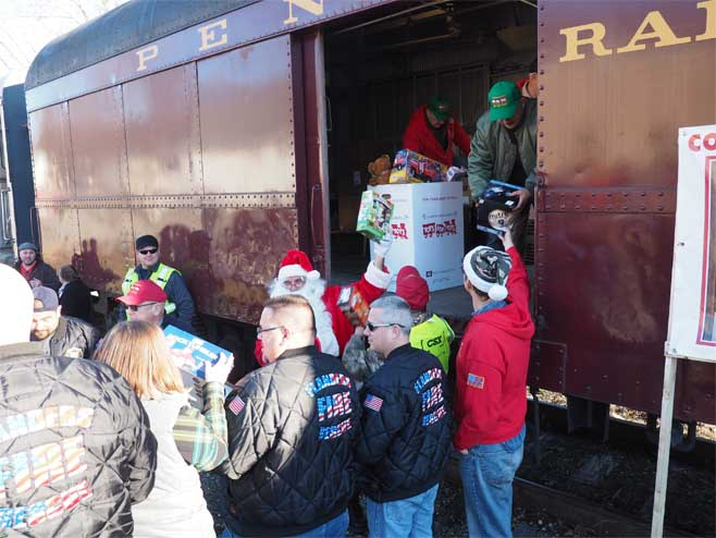 Flanders (NJ) firefighers help load toys on the Toys for Tots train.
