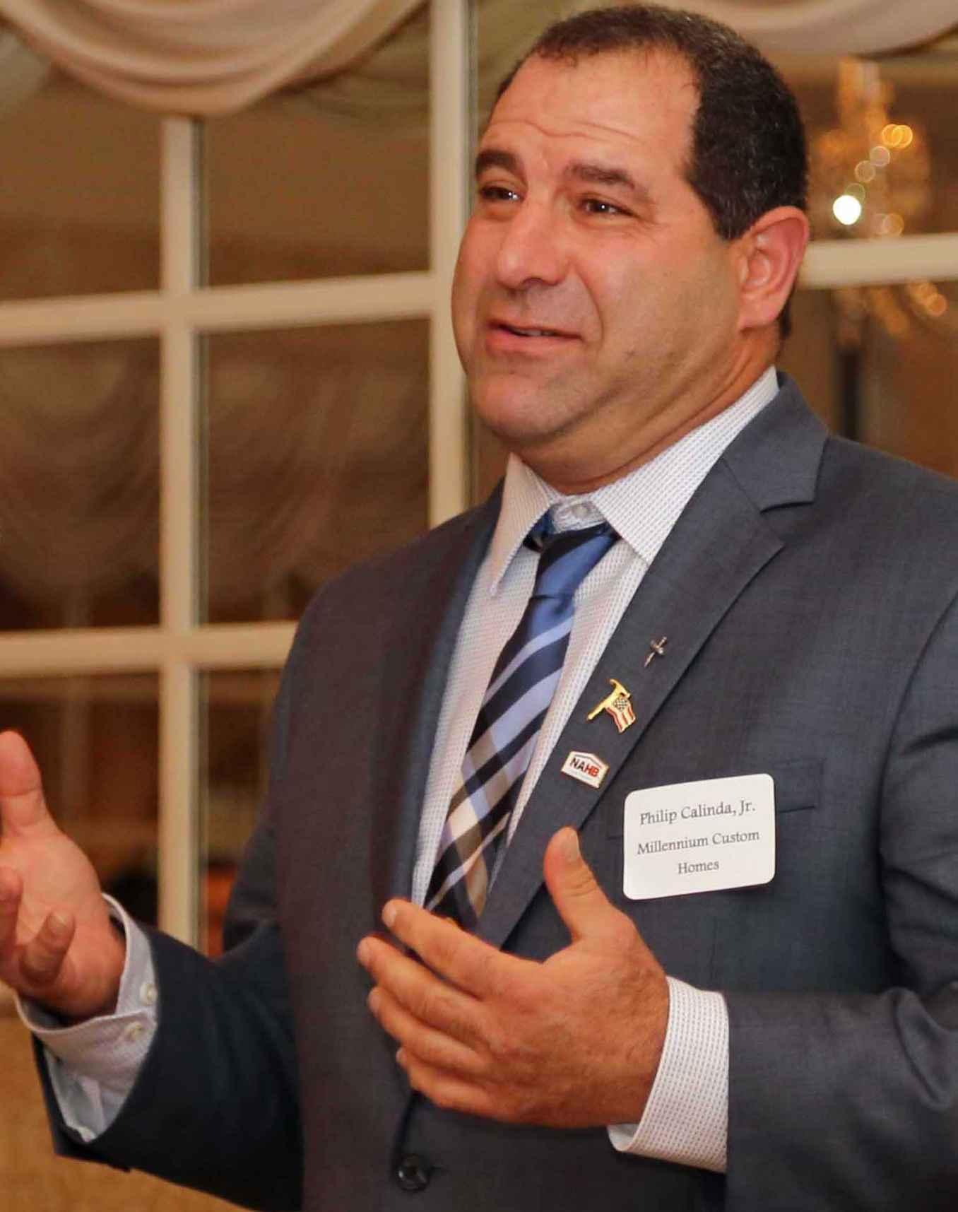 Phil Calinda Jr., head of the Metro Builders Association, talks with members.