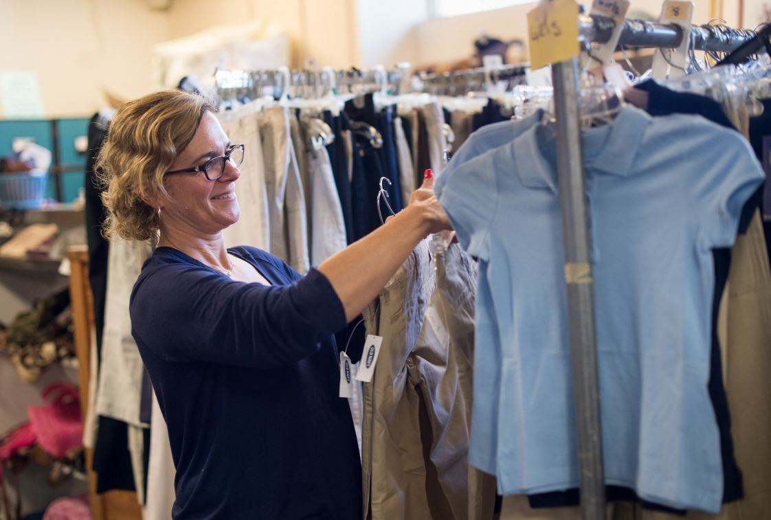 Acts 4 Ministry Volunteer Coordinator sorts through donated school uniforms