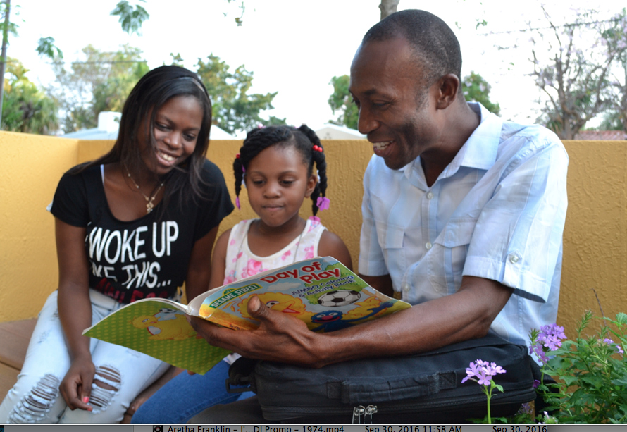 Henri Francois with daughters reading in Miami.Photo Credit: Emmanuel Philogene
