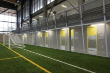 Woven metal mesh separates the locker room corridor from the playing field