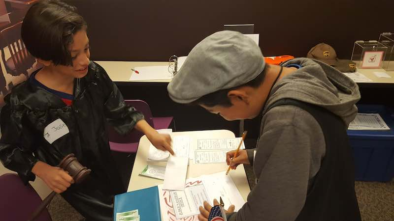 Jose, the Judge of Young AmeriTowne On the Road, at work in Towne Hall