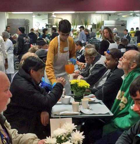 Volunteer serving juice to guests at the Good Shepherd Easter Meal 2016