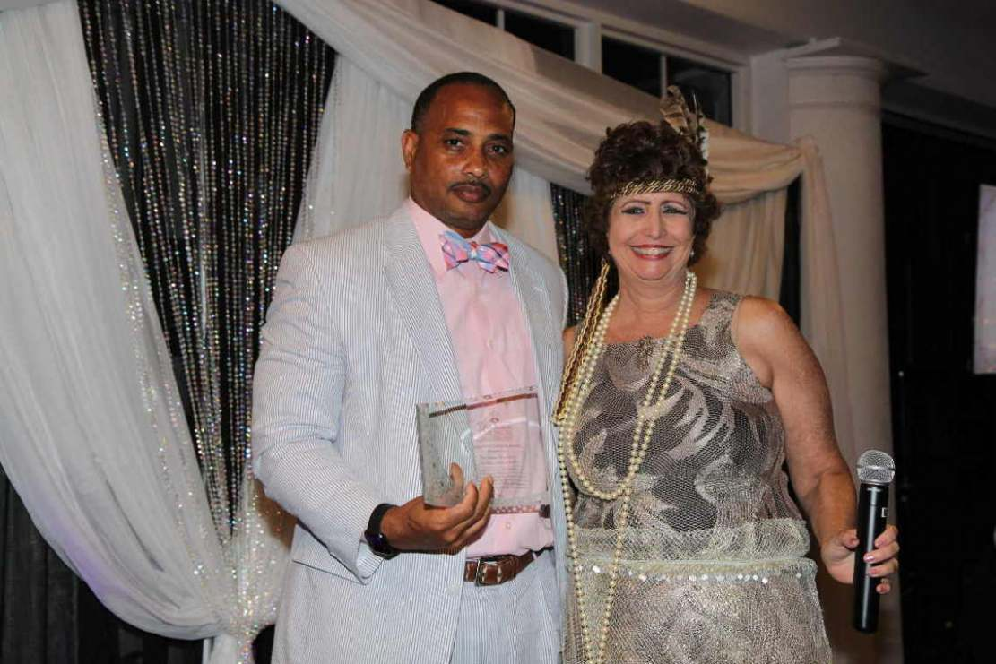 Dr. Jesse Bryson receives Teacher of the Year award from Dr. Karen Serrell