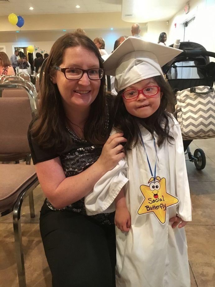 Preschool graduate with parent.