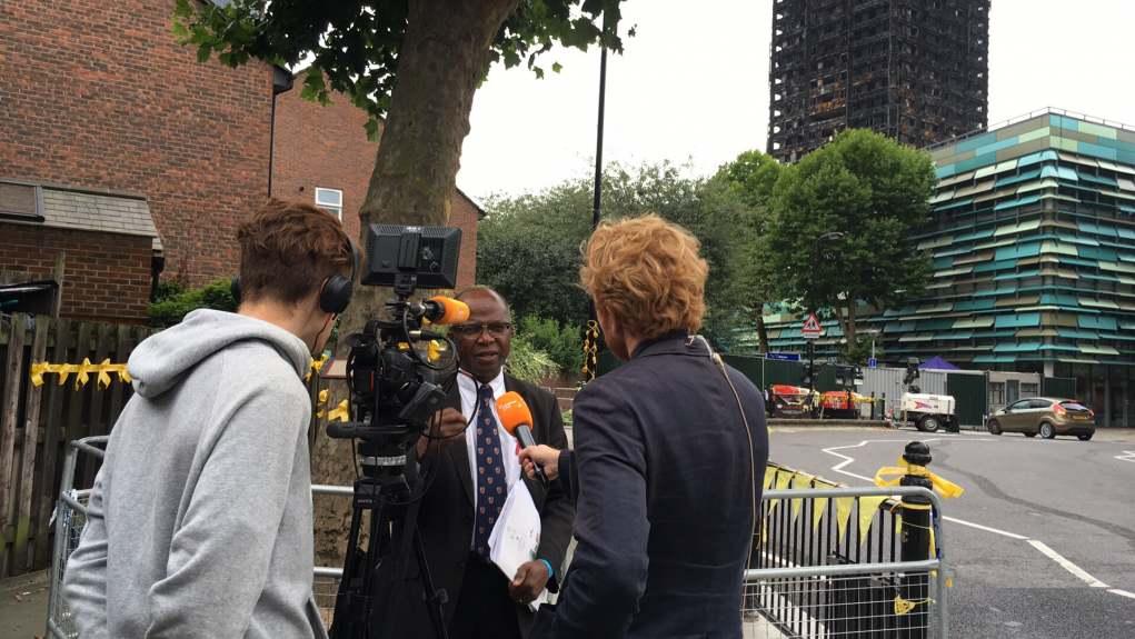 Professor Chris Imafidon speaking in the shadow of burnt London's Grenfell Tower
