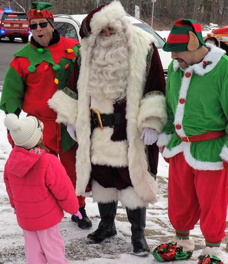 A little girl talks to Santa and his helpers about gifts and other topics.