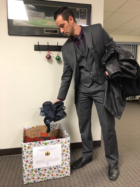 Votion Manager Cristian donates items to the company's winter clothing drive.