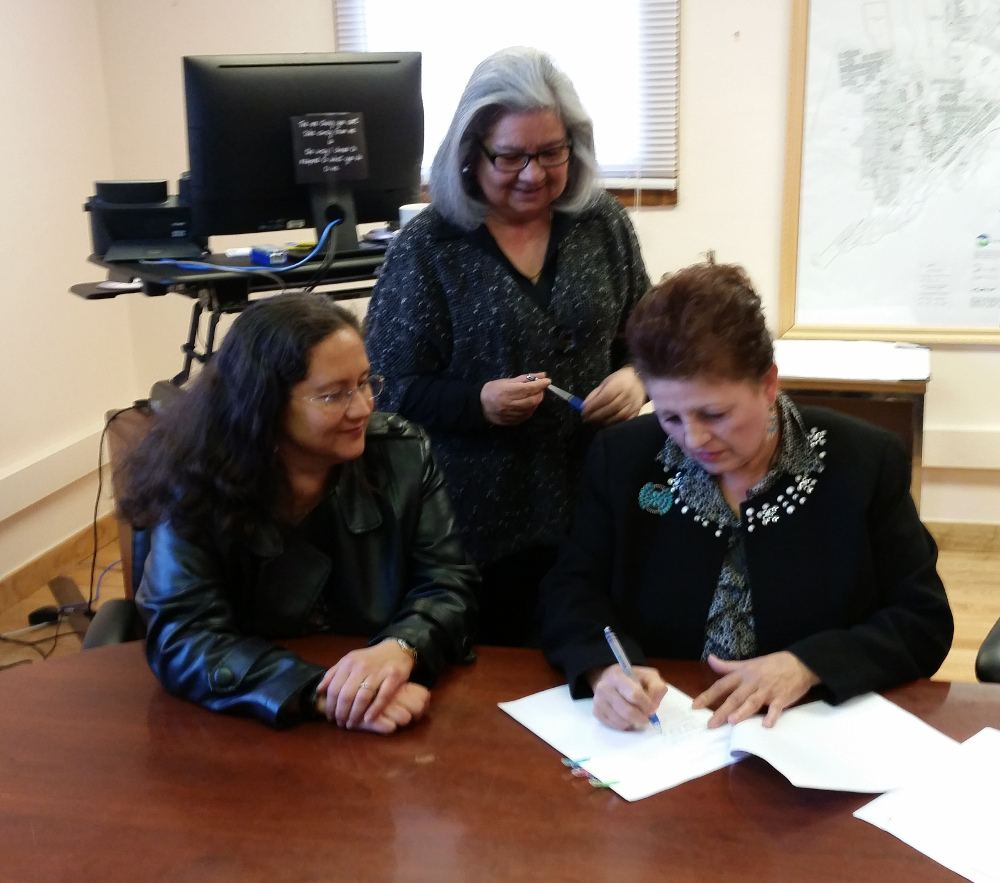 Mayor Tonita Gurule-Giron, at right, signs contract