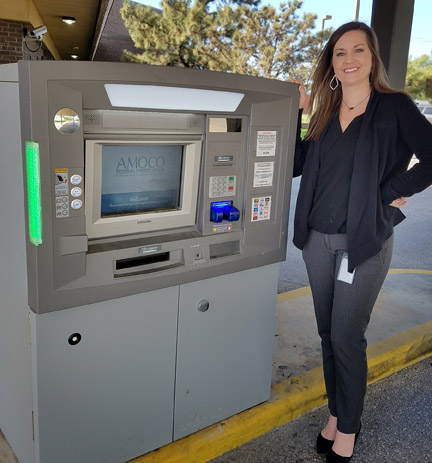 Ashley Carner, COO of AMOCO FCU, next to an ATM, which Dolphin Debit manages
