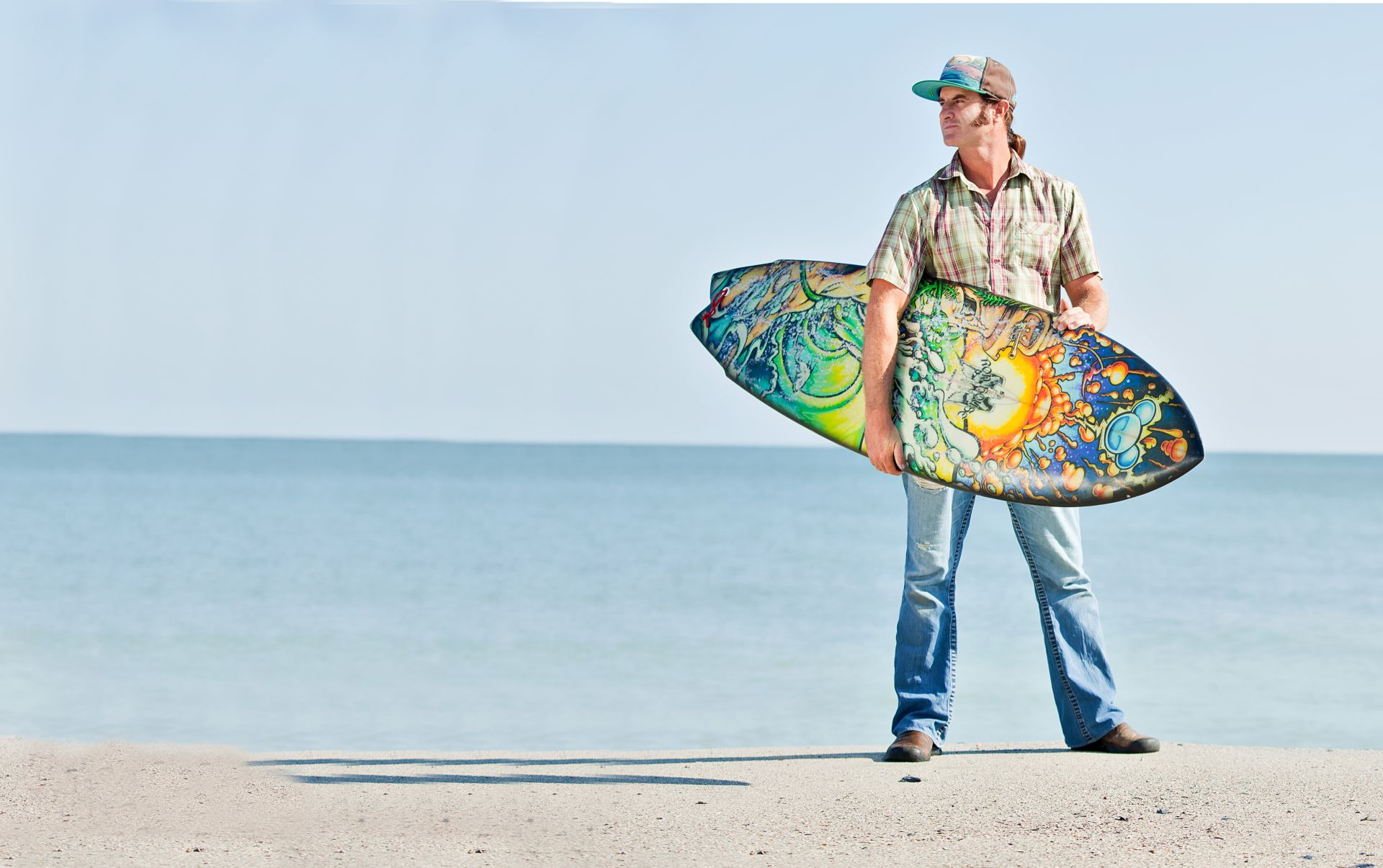 Surf Artist Drew Brophy holding his painted Surfbo