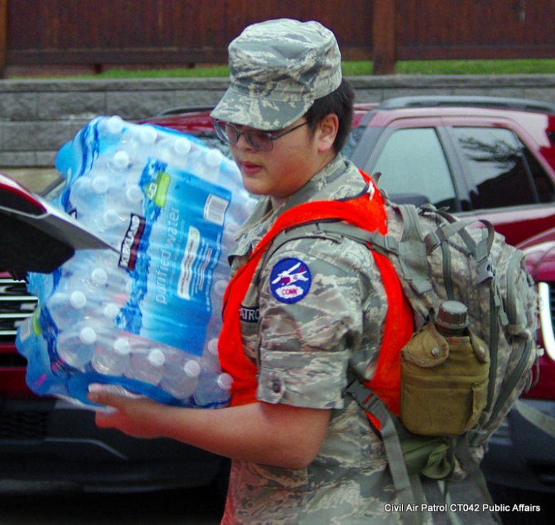 C/TSgt. Kiefer Jenkins loads a case of water into a vehicle.(Credit: Maj Milano)