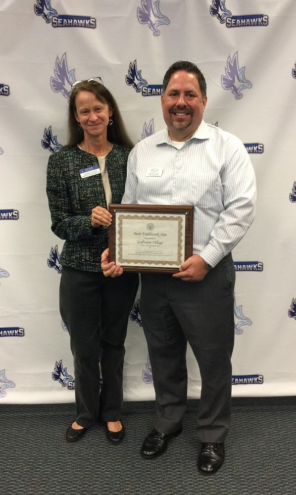 Keiser's Dr. Tina Gelpi presents award to Gulf Coast Village's John Nicolette