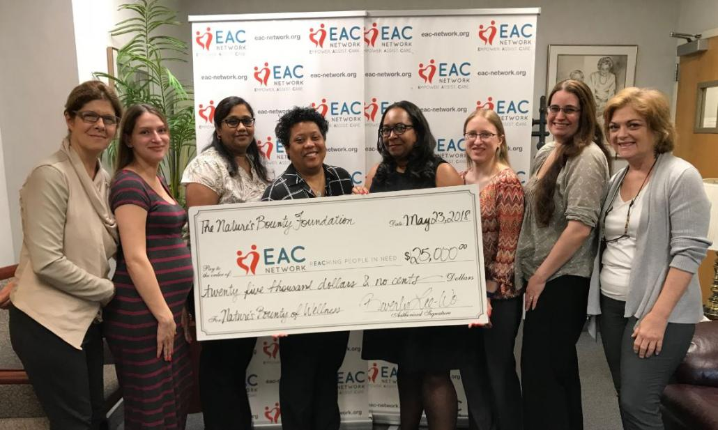 Beverly Lee-Wo presents check to EAC Network employees.