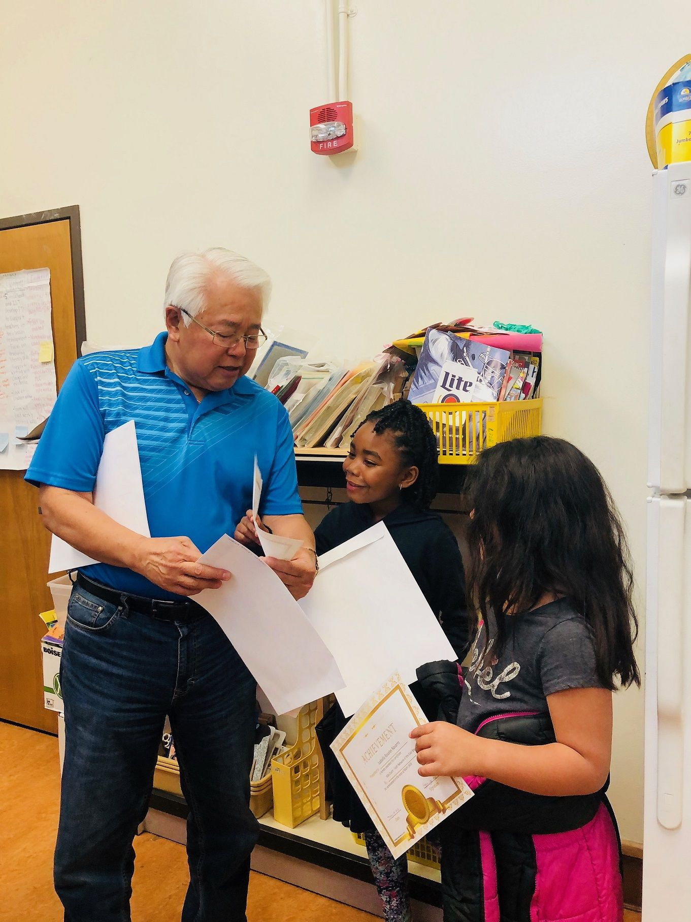 Kids Count math tutor Wilson Leong celebrates with students at Laurel Elementary