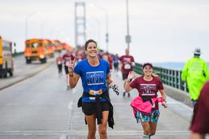 Michelle Coss crosses the finish line at the Labor Day Mackinac Bridge Run