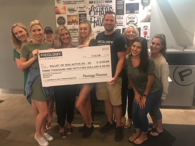 Pieology Pizzeria owner Kris Olsen presents donation to Valley of Sun.