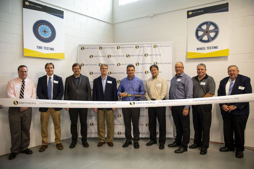 Dr. Jim Popio cuts the ribbon surrounded by local officials and tire executives.