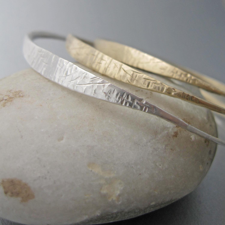 'marea alta' bangles in silver and bronze