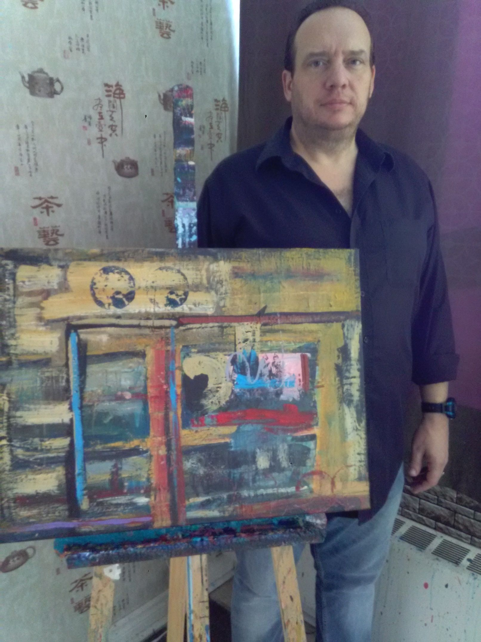 Carl Parker with his painting, Rustic Place