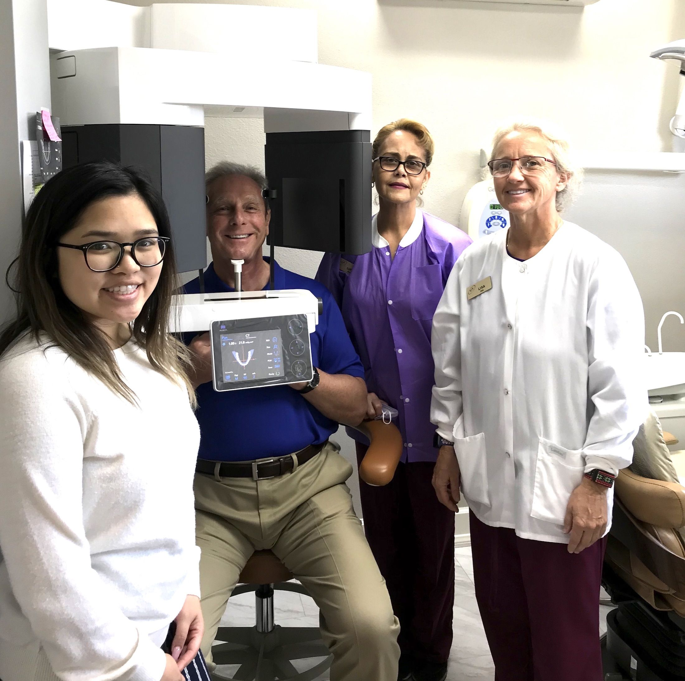 Dr. Kepic, second from left, with team members, showing 3D x-ray machine