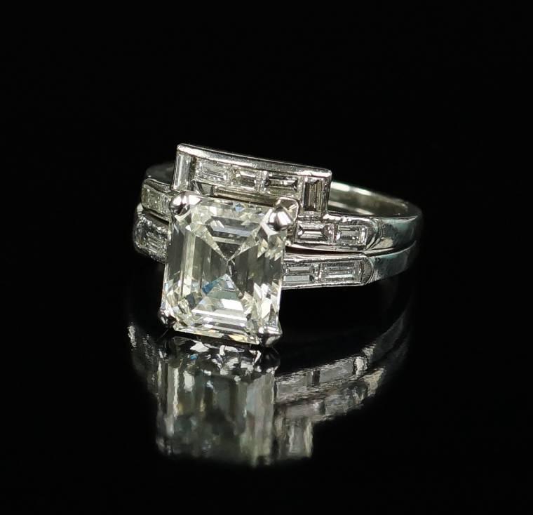 Stunning engagement ring set boasting a 3.28-carat emerald cut center diamond.