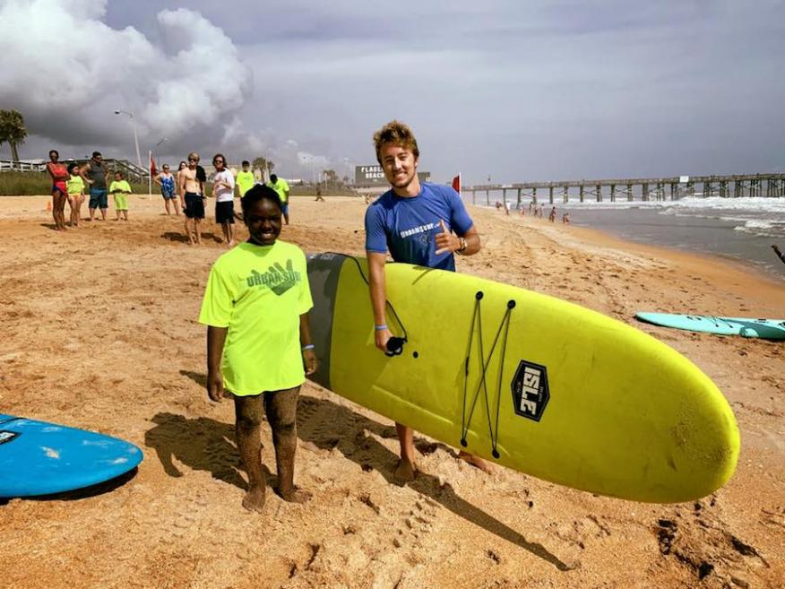 Volunteer Dalton Dalecki with a Surf Camp attendee.