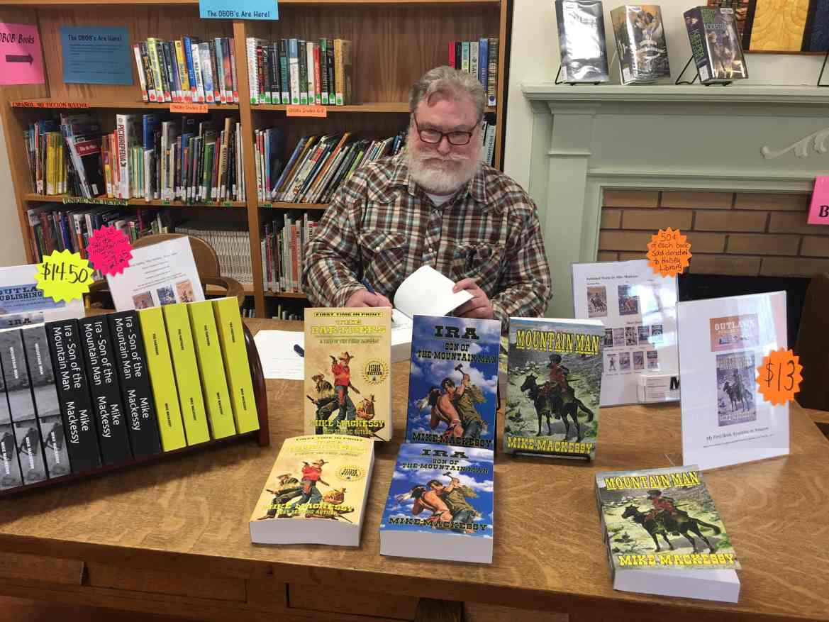 Mike Mackessy Sits With His Bestsellling Western Titles.