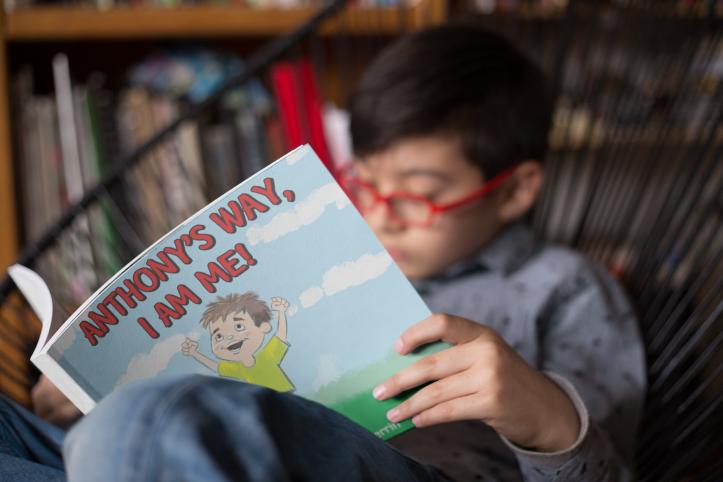 A boy reading Anthony's Way, I AM ME!